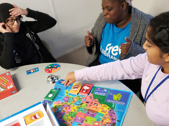 LEAP staff and students playing a board game with a graphic map of the United States on the board