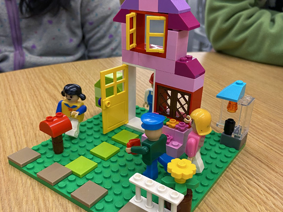 A scene created from LEGOs with three minifigs, a mailbox, flowers, white picket fence, and a pink house constructed from blocks