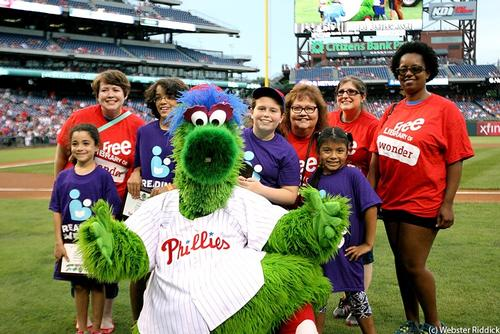 Summer Reading stars and their nominating neighborhood librarians pose with the Phillie Phanatic at Citizens Bank Park.