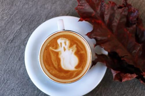 An autumn coffee cup with a foamy ghost