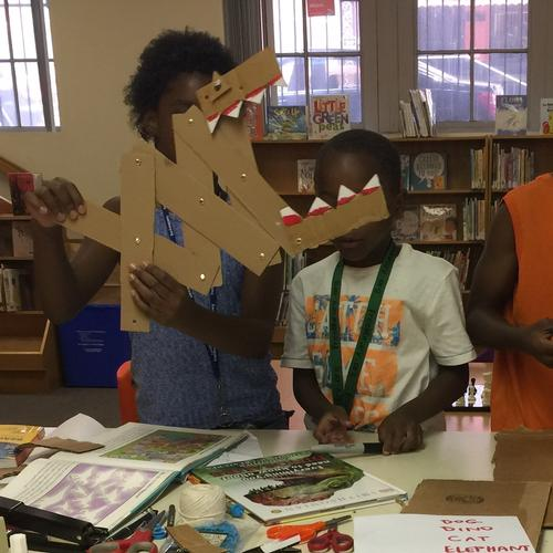 Children at Queen Memorial Library design impressive creations with cardboard and paper fasteners.