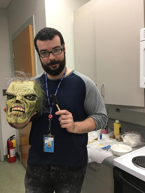 Joseph Torres, LA at Fumo Family Library, with his zombie, created with cardboard, glue ,and hair from an old prop wig.