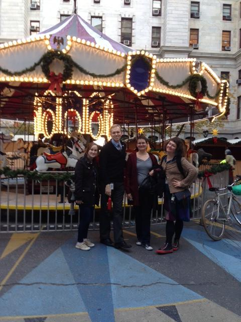 Ms. Liz, Mr. Chris, Ms. Liz, and Ms. Kate in front of carousel in City Hall courtyard.