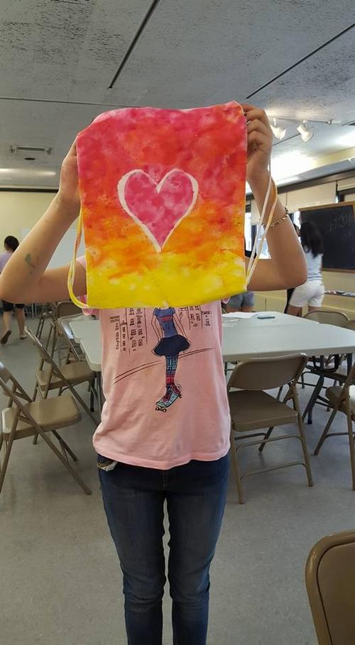 A teen patron holds up a bag she designed at Independence Library.