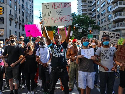 Photo of Black Lives Matter protest with a man holding a sign that says: The Revolution Will Be Streatmed