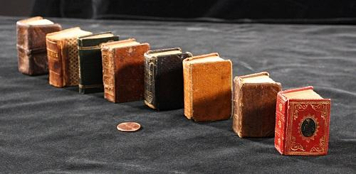 Miniature books lined up with a penny for scale