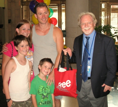 Louis Baker and his children Alyssa (15), Eric (9), and Christopher (4) pose for a photo with Director of Library Operations Joe McPeak.