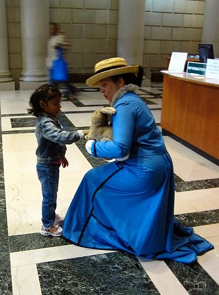 A member of the Beatrix Potter Society dressed as Beatrix, with Peter Rabbit, greets a young library patron. Photo courtesy of Jenny Walker.