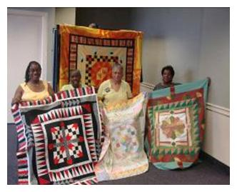 Members of Quilters of the Round Table displaying their work. Image source: qrtphilly.com