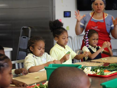 Students interact with produce while an Nourishing Literacy instructor speaks