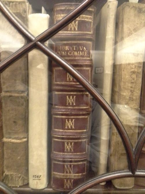 Horace. Opera book behind glass, wooden bookcase.
