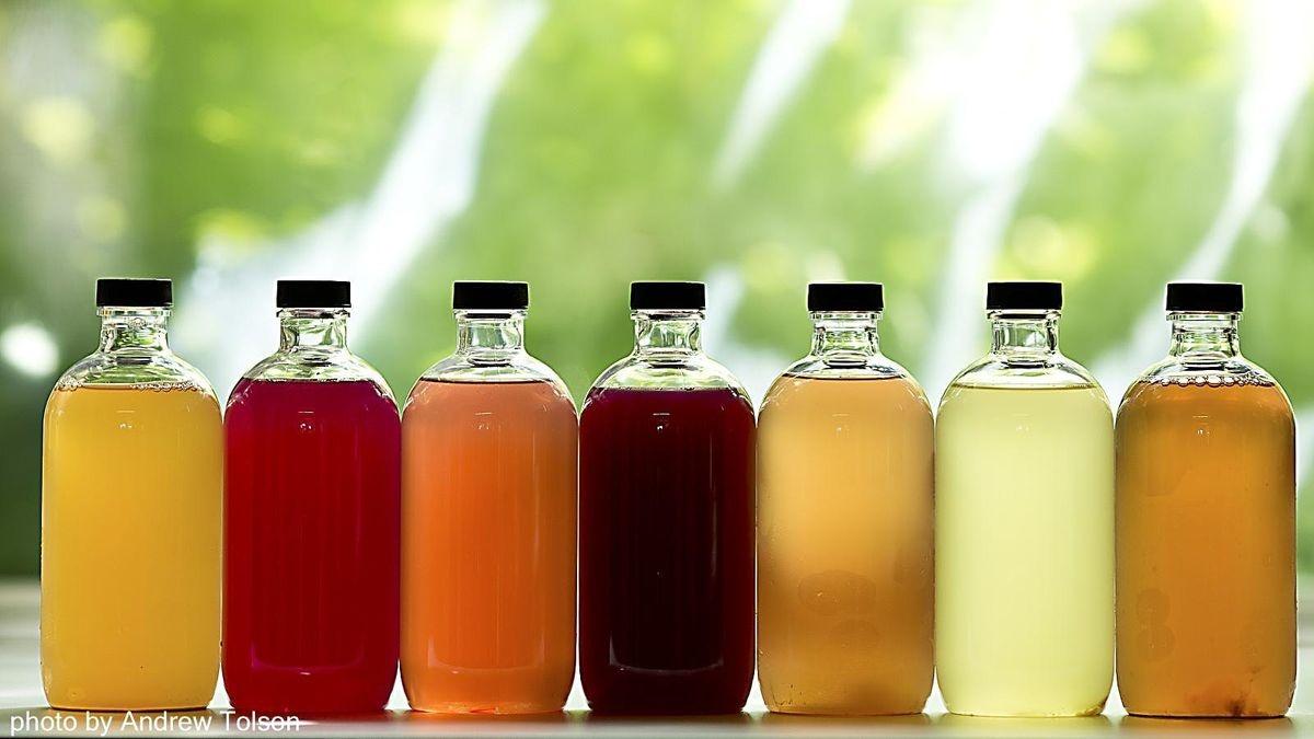 seven bottles containing different color liquids