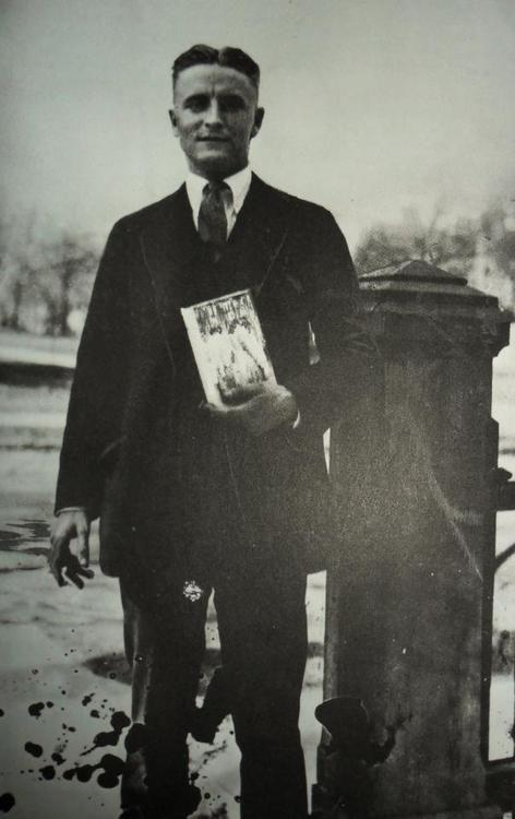 F. Scott Fitzgerald holding a copy of <i>The Great Gatsby</i>