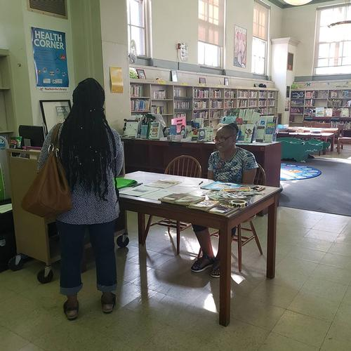 Pat Erwin-Blue, a Resident Consultant Team member, talking to a visitor at Paschalville Library.