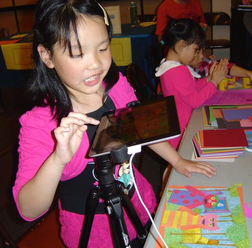A young attendee uses an iPad to create images for stop motion animation.