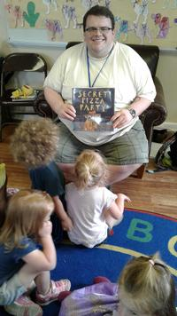 Mark Costello reads to a group of children.