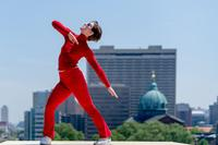 A dancer practicies Brown's <i>Roof Piece</i> against the Philadelphia skyline.