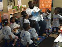 Jazz the Barber reads to some children at his business, Creative Image Unisex Salon.