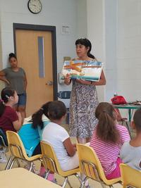 Linda Maldonado conducts a story time with a group of children.