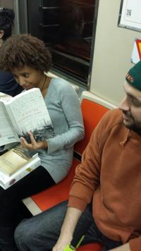 The author engrossed in some historical fiction while riding the subway.