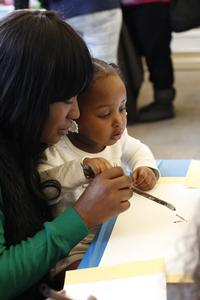 A family uses ink to paint a scroll after a lesson from the Philadelphia Zoo and the Philadelphia Museum of Art.