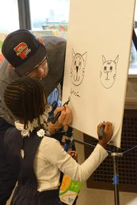 Artist Greg Pizzoli draws with a child at the Summer of Wonder Kickoff.