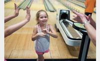 A Summer Reading participant prepares to high five her team at Torresdale Library's 10th annual Read, Eat, and Bowl.