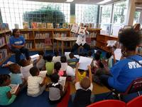 Summer Reading Outreach Specialist Rich Torrance reads to a group of kids at West Oak Lane Library
