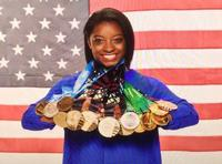 Simone Biles pictured with her many, MANY medals!