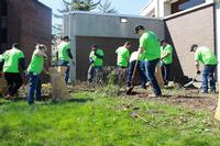 Volunteers from PECO help clean the grounds of Overbrook Park Library.
