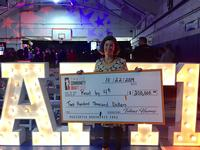 Jenny Bogoni of Read by 4th holds up the generous donation from Tobias Harris during his Community Draft.