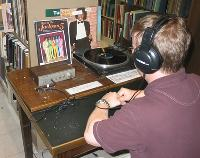 A patron listening to an LP on one of our turntables