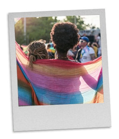a Polaroid style photo picturing two figures draped beneath a rainbow shawl