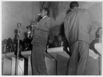 The Jimmy Heath Orchestra performing in 1947, Jimmy conducting, Charlie Parker sitting in, and John Coltrane between them, watching his hero wide-eyed