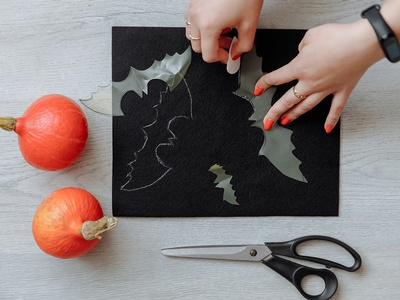 a set of hands cutting out a bat shape from black construction paper